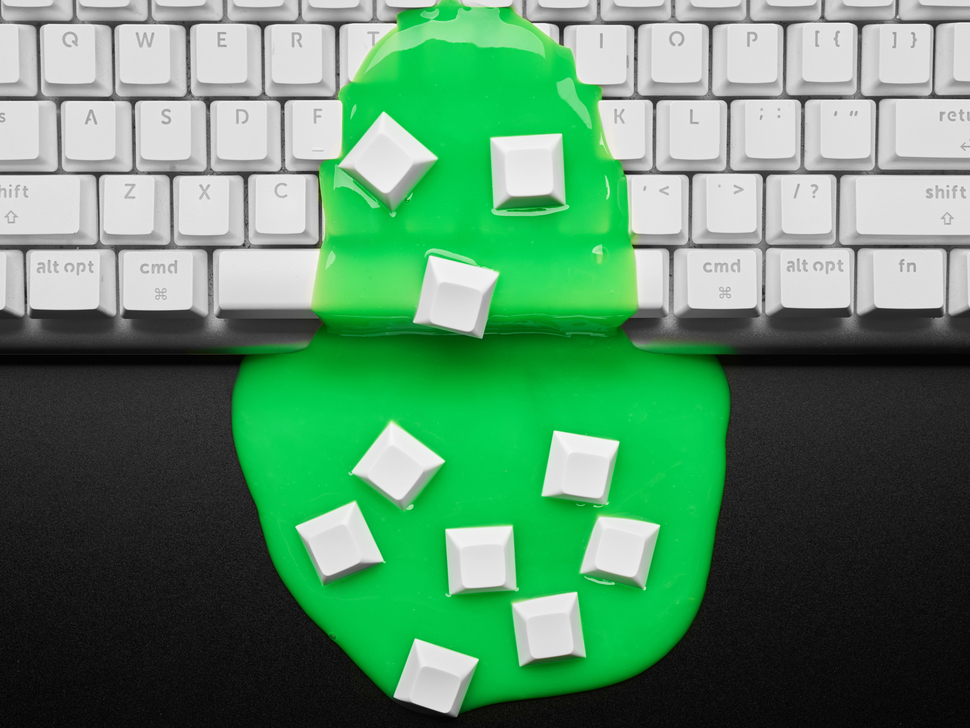 Top view of a white keyboard covered with green gooey slime topped with white keycaps.