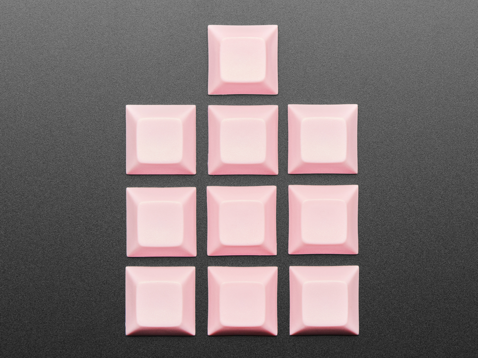 Top view of 10 pink plastic keycaps.