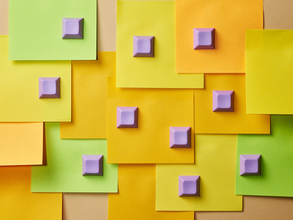 Top shot of 10 purple keycaps spread out on green, orange and yellow post it notes.