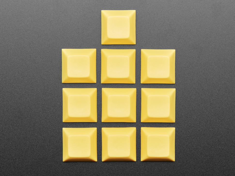 Top view of ten yellow plastic keycaps.