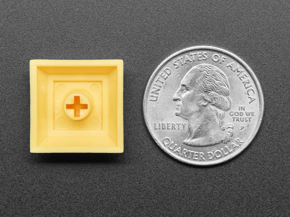 Bottom of yellow plastic keycap next to US Quarter.