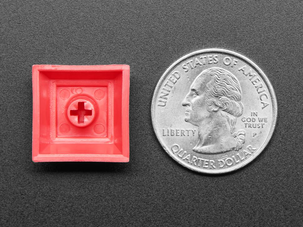 Bottom of DSA red color keycap  next to US quarter.
