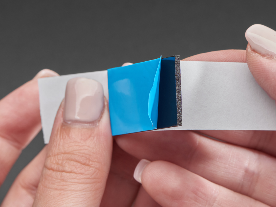 Close-up of a hand pulling apart both sides of the rectangular foam tape adhesive.
