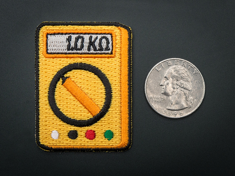 Rectangular embroidered badge in the shape of orange multimeter with dial, and a grey screen reading 1.0 kilohms. Next to quarter for scale