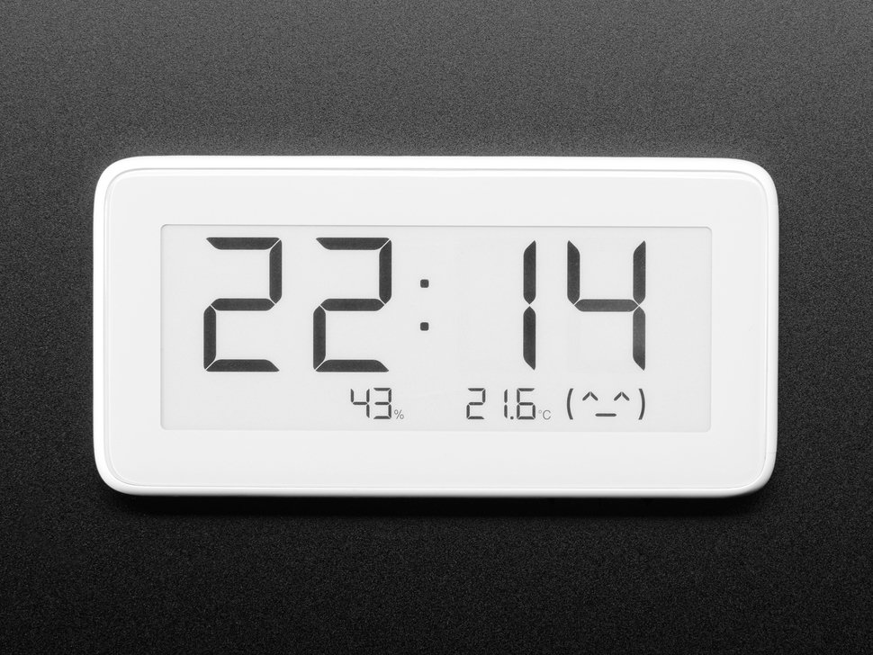 Top view of white rectangular digital clock with electronic ink display. The display reads the time, 22:14, along with 43% humidity, 21.6ºC with a smiley emoticon.