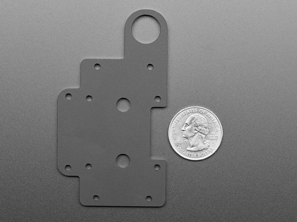 Acrylic mounting plate next to US quarter.