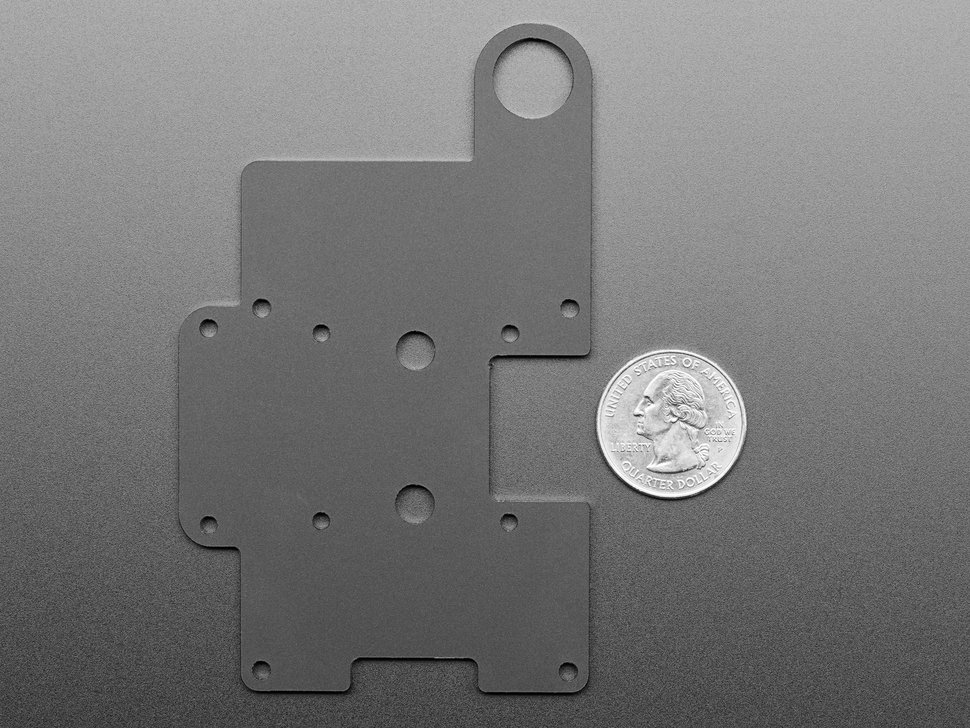 Top view of acrylic mounting plate next to US quarter.