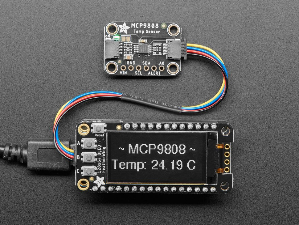 "Top view of temperature sensor breakout above an OLED display FeatherWing. The OLED display reads ""MCP9808 Temp: 24.19ºC"""