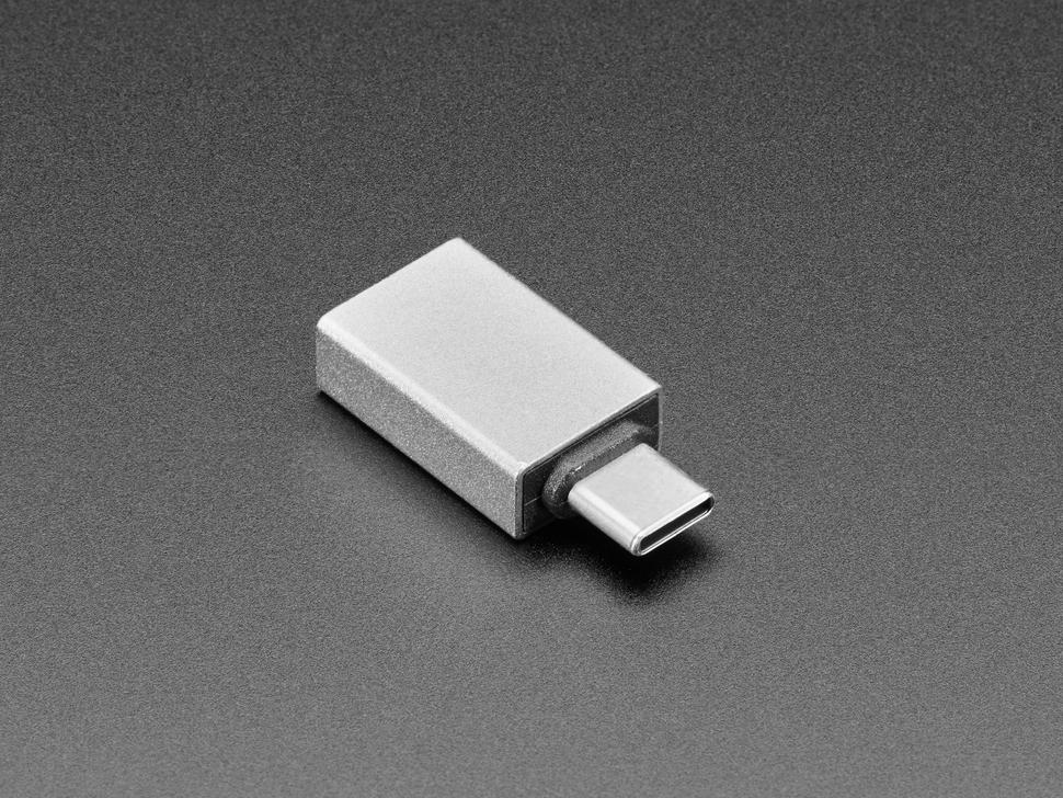 Reverse angled shot of gray rectangular USA A socket to USB C plug adapter.