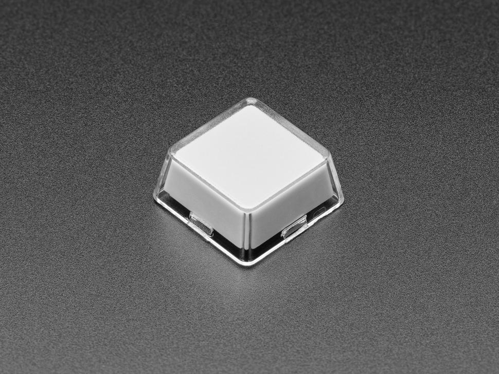 Angled shot of single white plastic keycap.