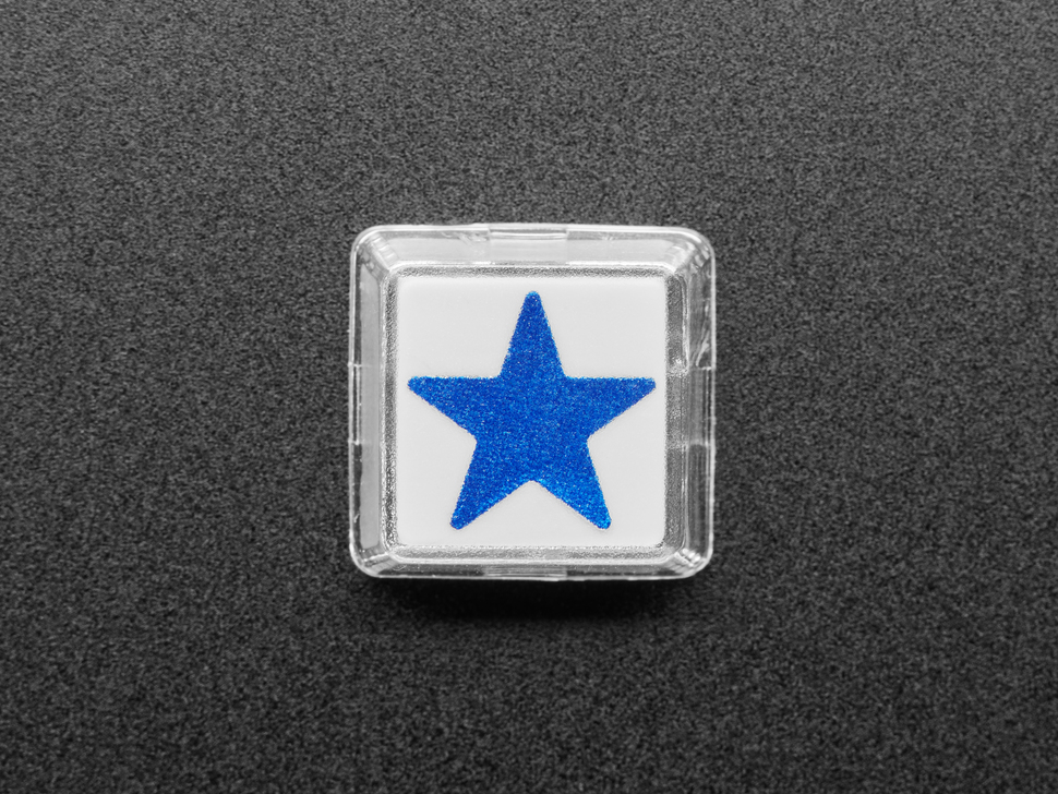 Top view of single white plastic keycap with a blue star sticker.