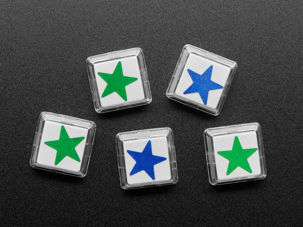 Top view of five white plastic keycaps with blue and green star stickers.