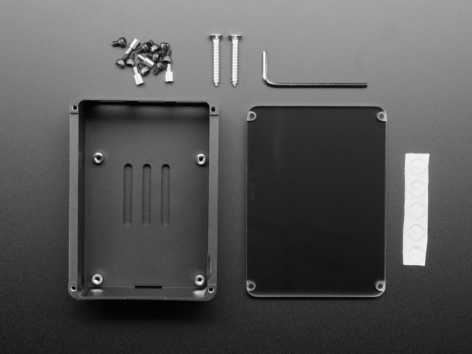 Top view of black aluminum parts, rubber feet, and hardware for a Raspberry Pi 4 case.