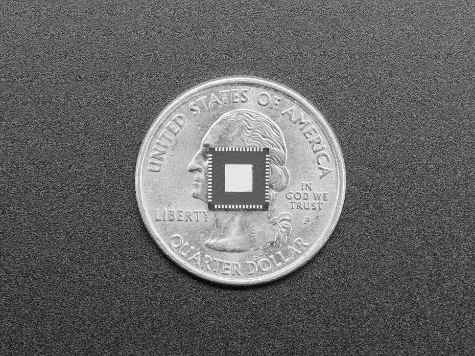 Bottom of single RP2040 microchip atop a US quarter for scale.