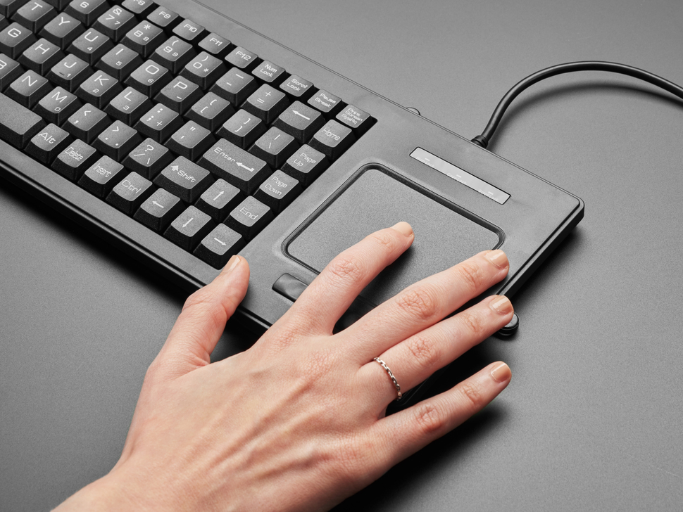 Angled close-up of a white hand using the trackpad.