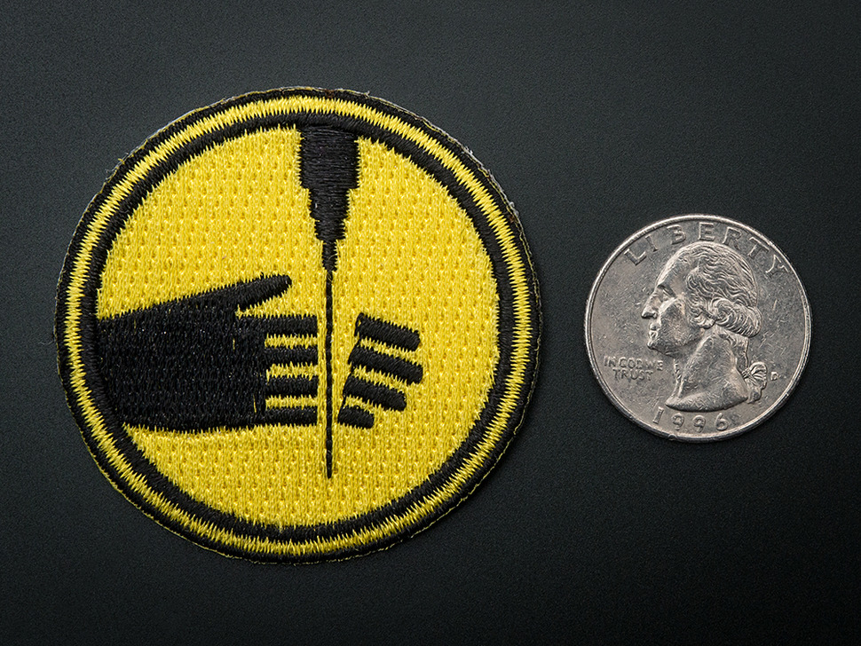 Closer view of water set skill badge,  with quarter for scale.