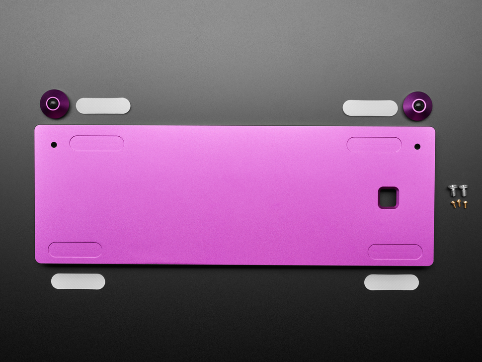 Top view of purple aluminum keyboard shell with purple aluminum bumper feet, four adhesive stickers, and mounting hardware.