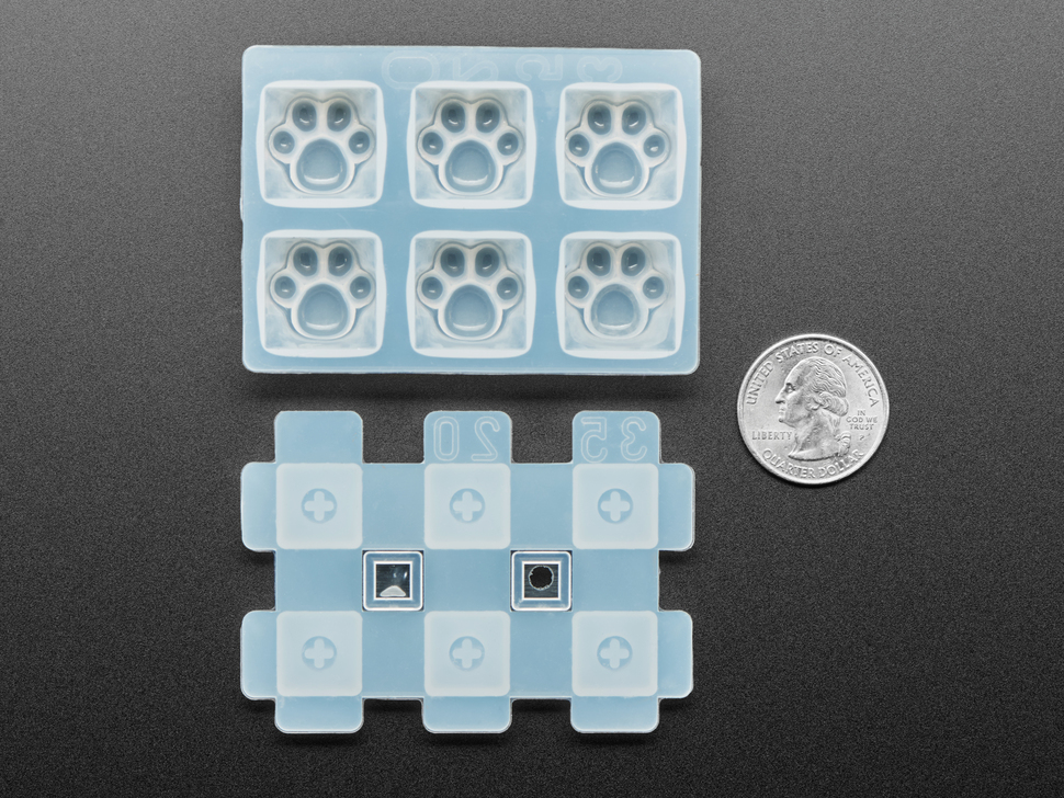 Top view of two-piece rubber kitty paw keycap molds next to US quarter for scale.