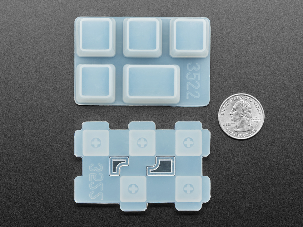 Bottom of two Tab keycap molds next to US quarter for scale.