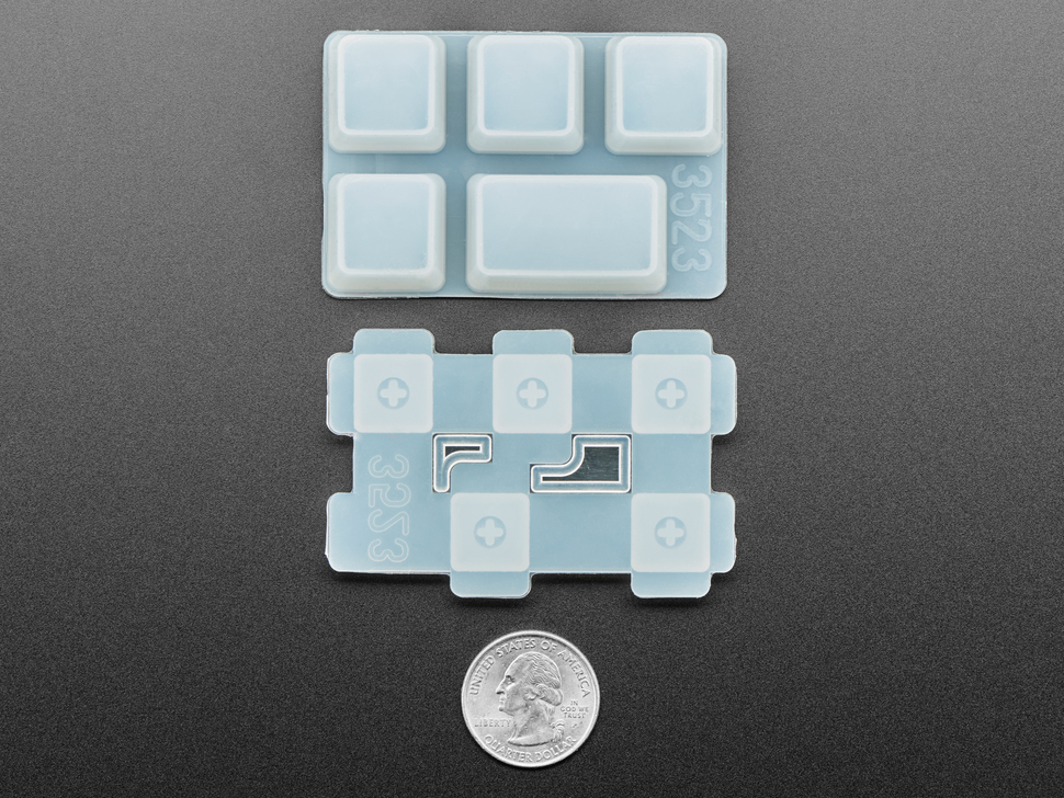 Bottom of disassembled Caps Lock keycap molds above a US quarter for scale.