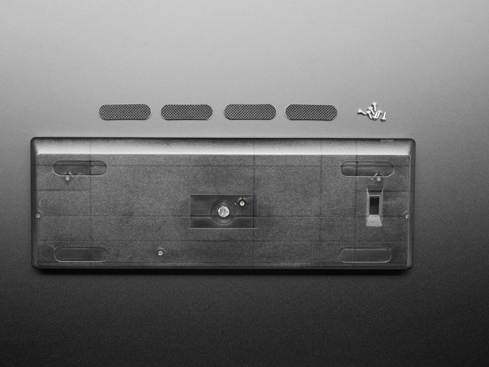 Top view of translucent smoke keyboard shell with four no-slip stickers and hardware screws.