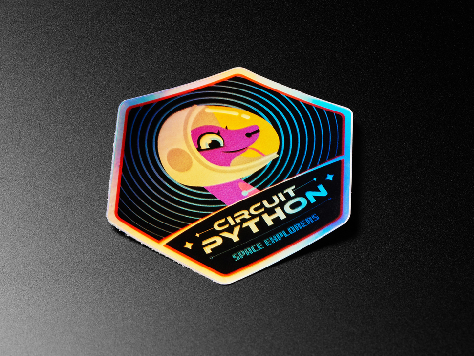 """Holographic sticker with friendly snake wearing a space-helmet. Text says """"Circuit Python Space Explorers"""""""