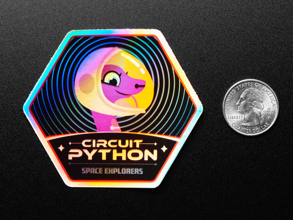 """A holographic sticker with friendly snake wearing a space-helmet. Text says """"Circuit Python Space Explorers"""" measured by a US quarter"""