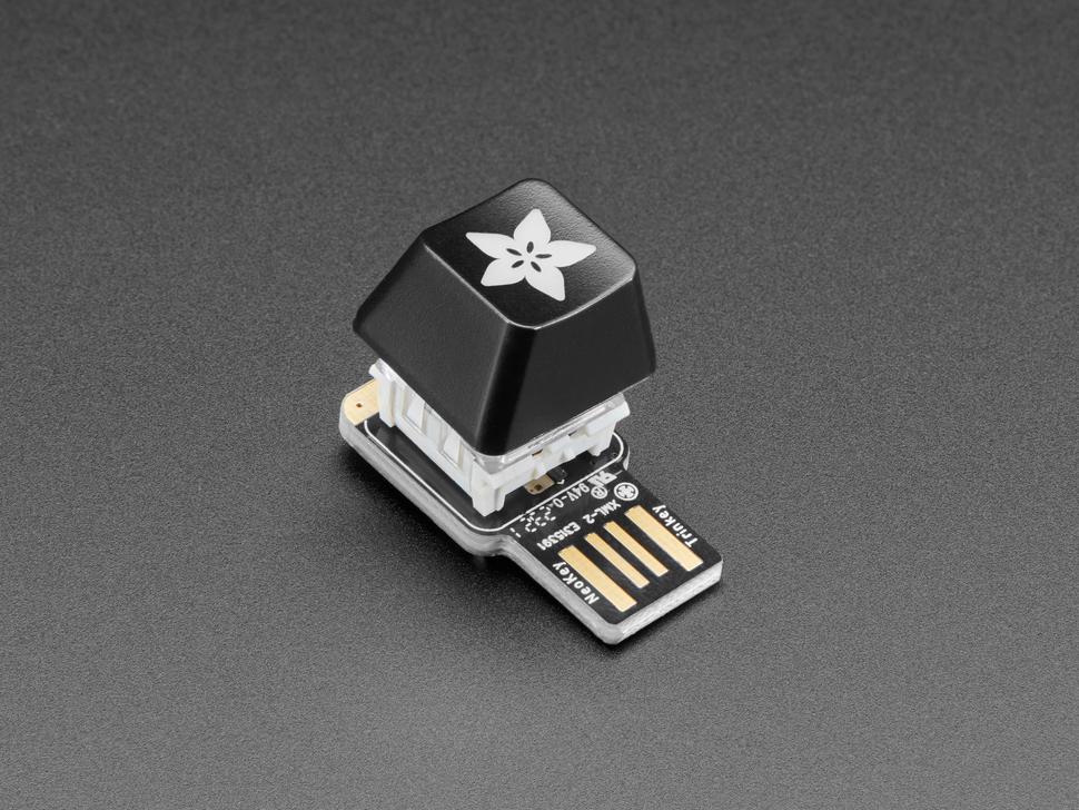 Angled shot of black Adafruit logo keycap on a TrinKey.