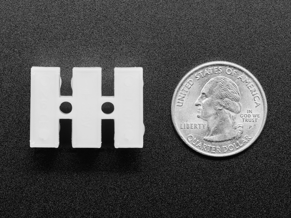 Bottom of single white 3-pin quick wire joint next to US quarter for scale.
