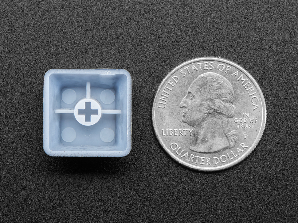 Bottom of keycap next to US quarter for scale.