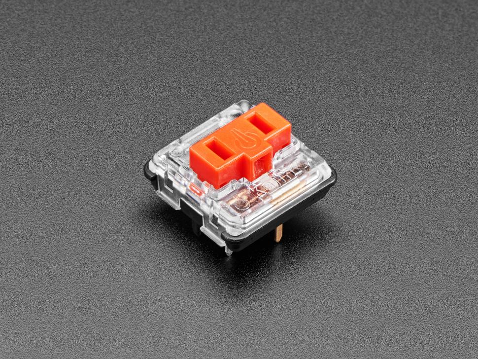 Angled shot of one red Kailh Choc V1 key switch.