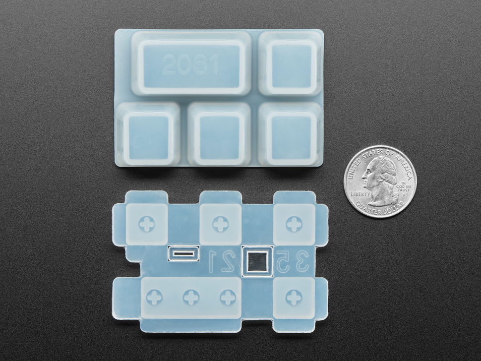 Bottom of keycap mold next to US quarter for scale.