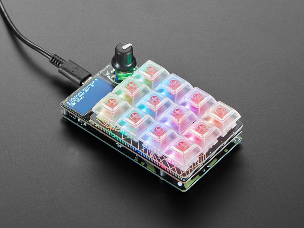 Angled shot of lit assembled MacroPal keypad glowing rainbow colors.