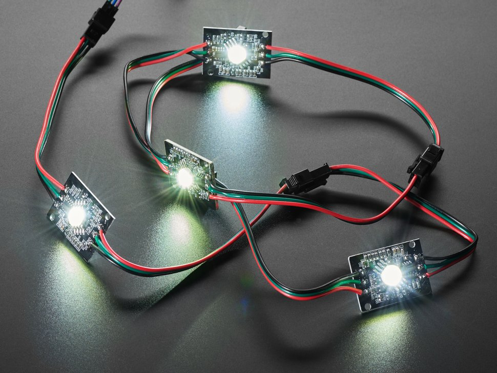 Four NeoPixel LEDs chained together, emitting cool white glow.