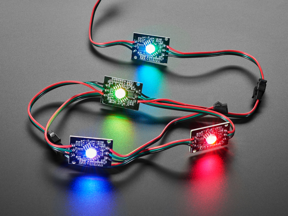 Four NeoPixel LEDs chained together, all emitting rainbow colors.
