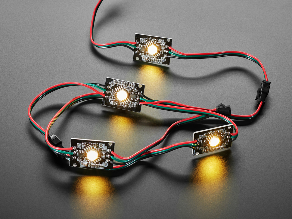 Four NeoPixel LEDs chained together, all emitting warm white glow.