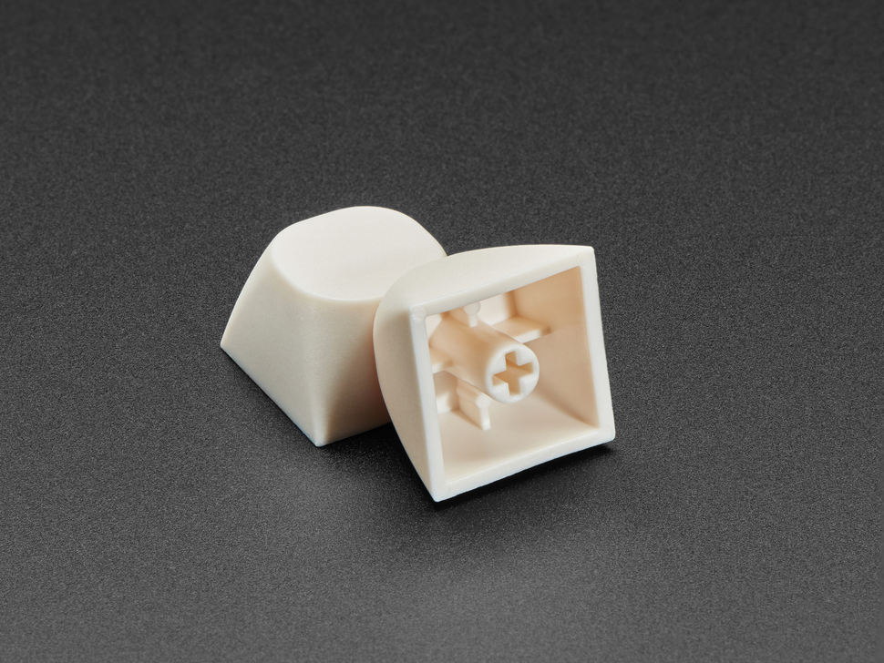 Angled shot of two milky white MA keycaps with one stacked against the other.