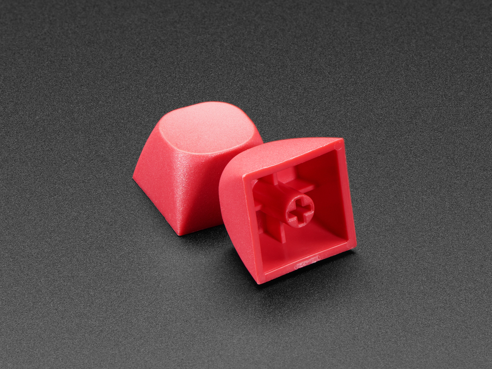 Two red keycaps stacked against eachother.