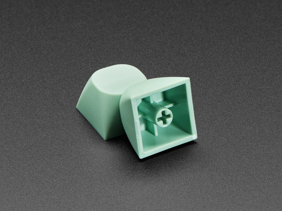 Two green keycaps stacked against eachother.