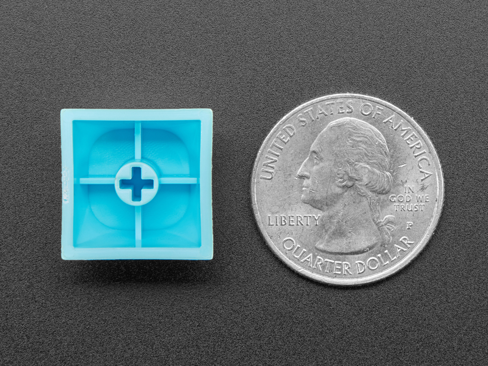 Bottom of cyan keycap next to US quarter for scale.