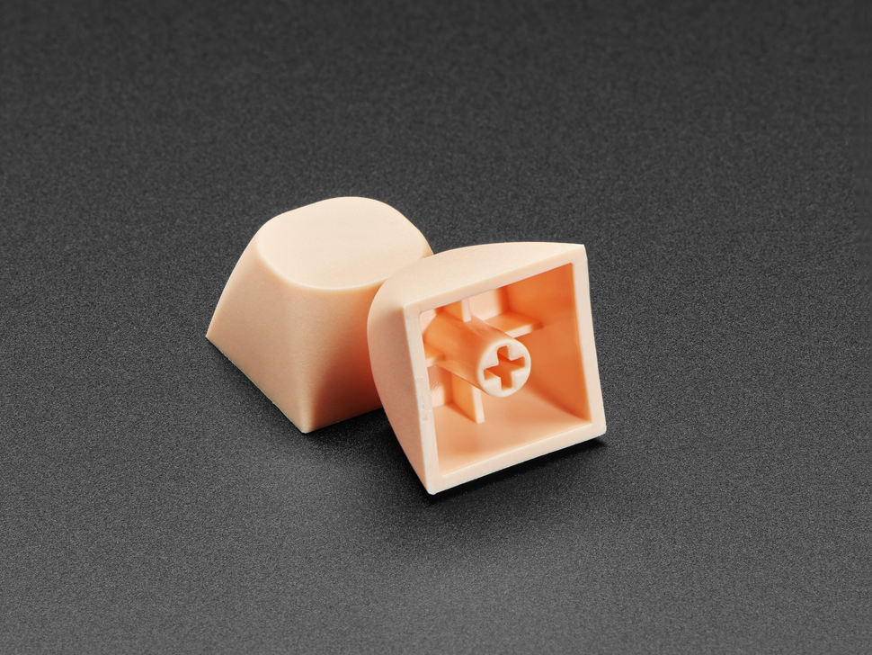 Two cream orange keycaps stacked against eachother.