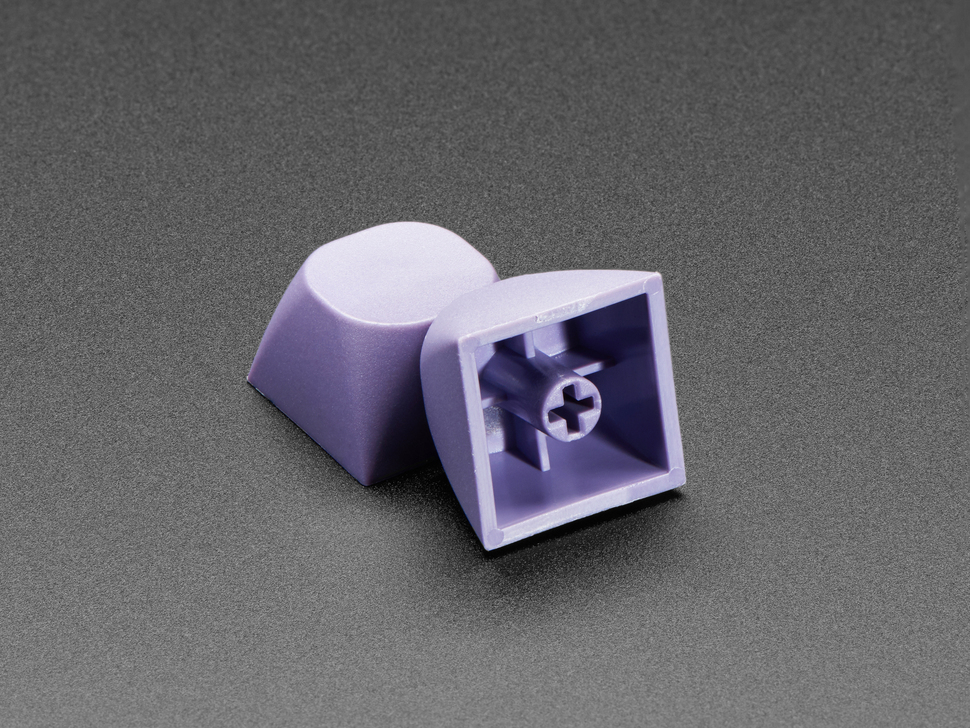 Two purple keycaps stacked against eachother.