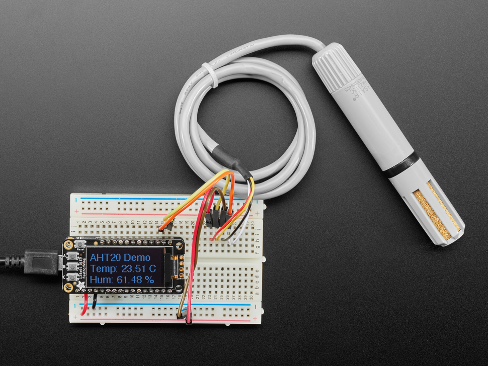 Top view of AM2315C sensor wired to a breadboard with an FeatherWing OLED display. The OLED shows the data from the temperature-humidity sensor.