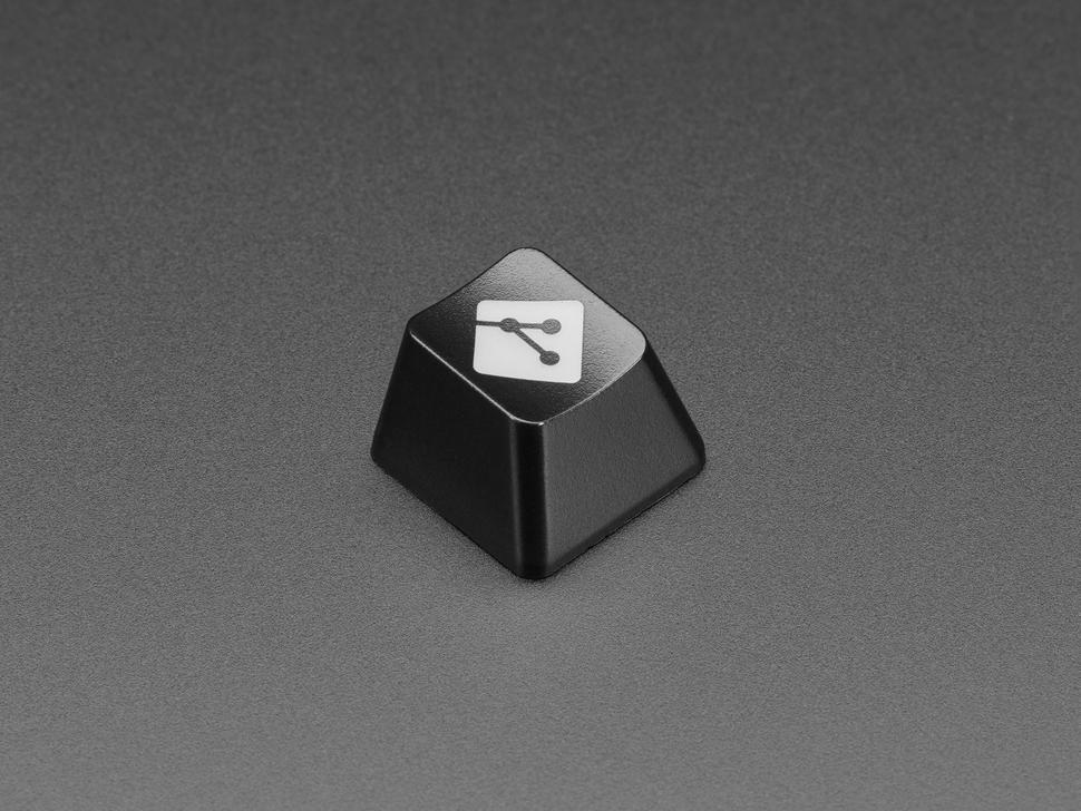 Angled shot of black GIT logo keycap.