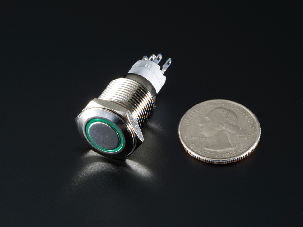 shot of rugged metal pushbutton with green led ring next to US quarter.