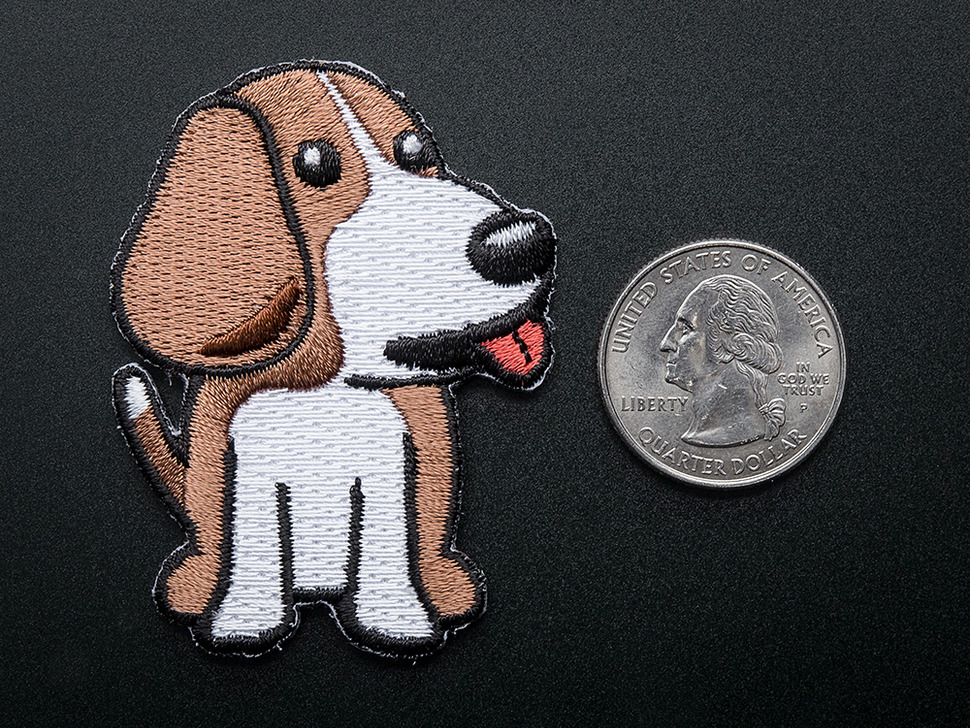 Embroidered badge in the shape of sitting BeagleBone dog.Dog is brown and white with red detail for tongue. Shown next to a quarter for scale.