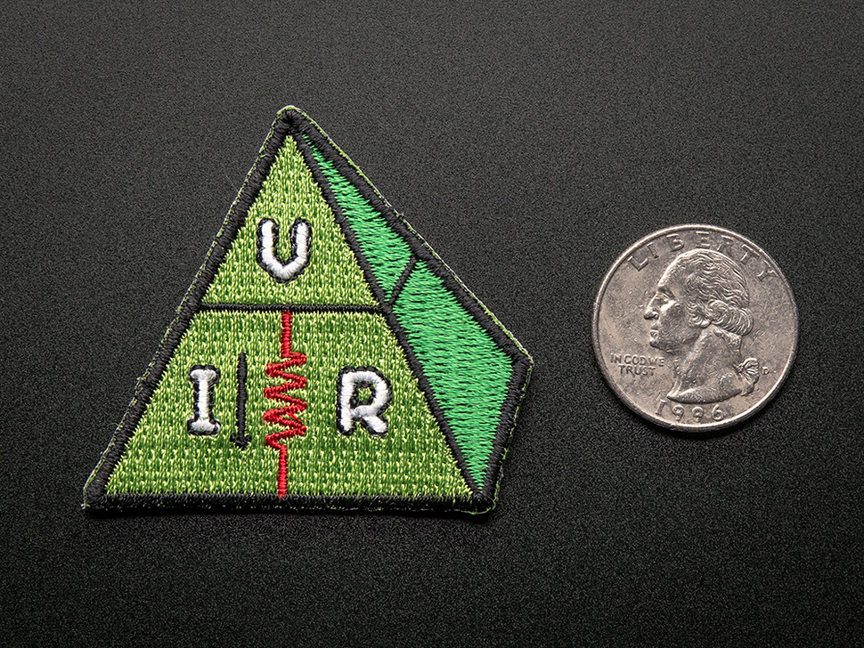 Embroidered triangle-ish shaped badge of a green pyramid with the letters V, I, and R in white, with a red zigzag resister, and trimmed in black. Shown next to a quarter for scale.