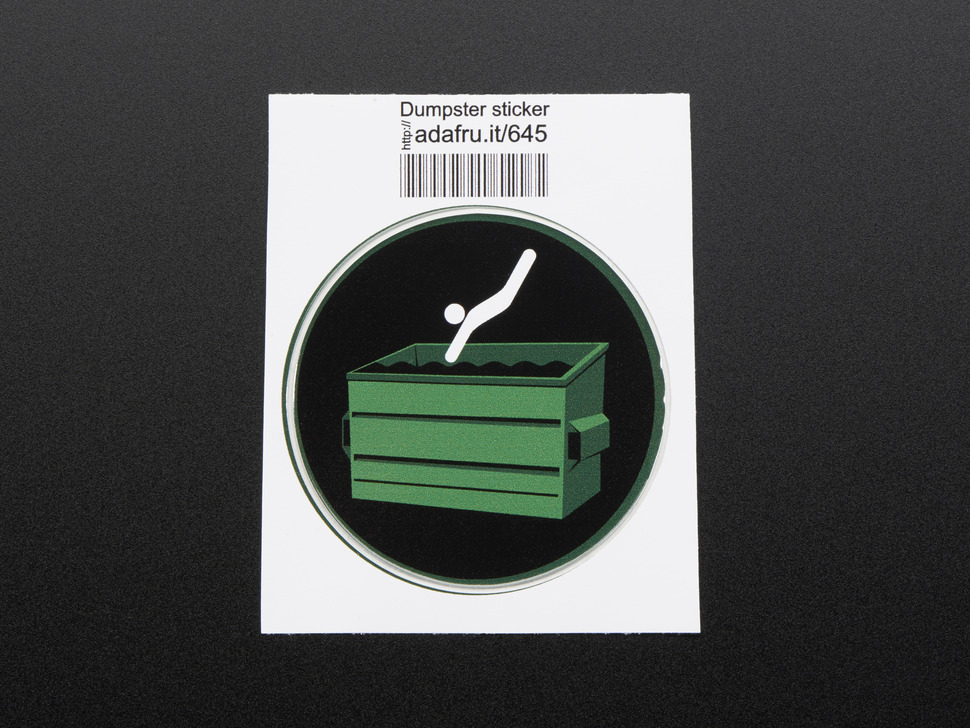 Circular sticker with green dumpster and a white stick figure mid-dive, on black background with green trim. Shown mounted on white paper with barcode.