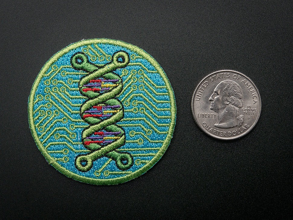 Circular embroidered badge showing a green double helix over an abstracted blue and green circuitboard design. Badge is trimmed in green and shown next to a quarter for scale.