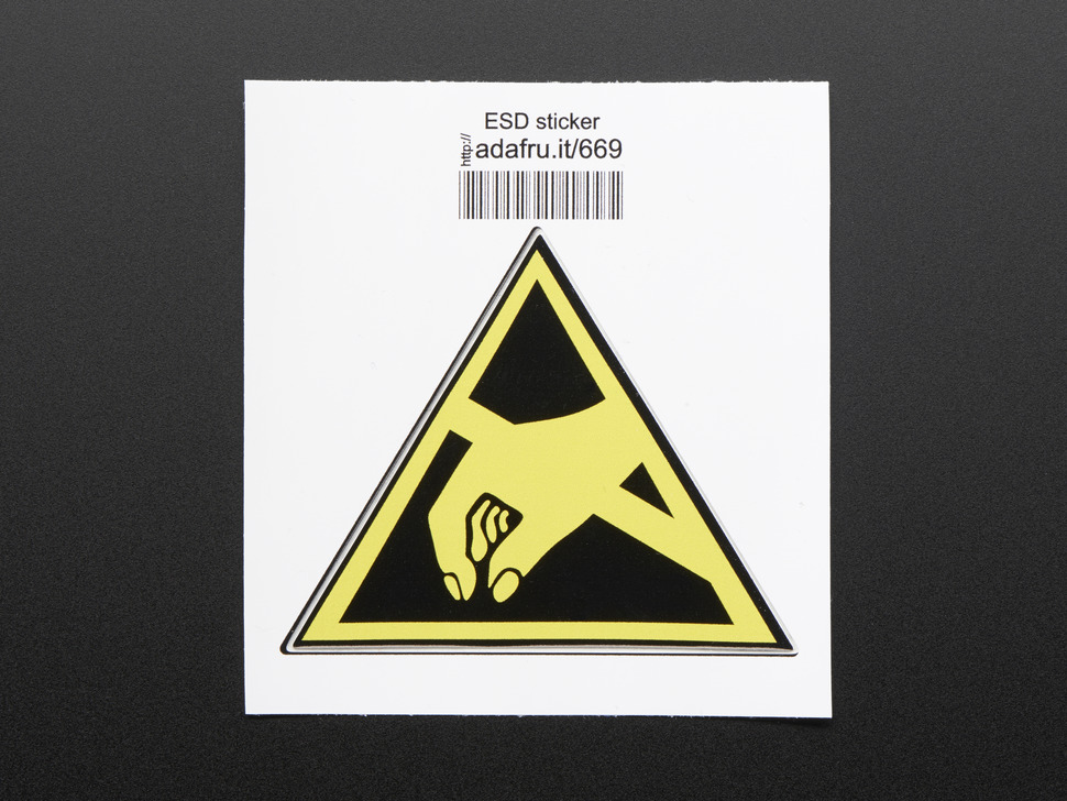 Triangle shaped sticker with yellow hand reaching to pick something up, over a black background, with yellow trim. Mounted on white paper with barcode